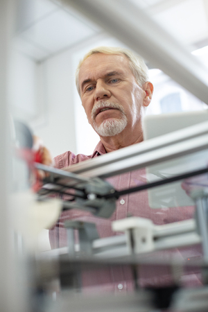 Close observation. Pleasant senior man observing the process of printing while looking inside the 3D printer