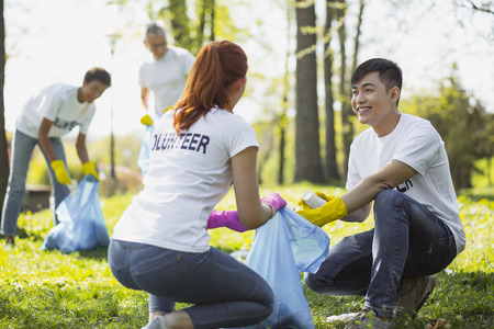 Environmental program. Nice two volunteers carrying garbage bag and looking at each other 免版税图像