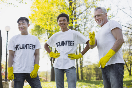 Involve in nature. Jolly three volunteers laughing and wearing gloves Banco de Imagens - 102433026