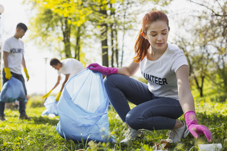 Community project. Beautiful female volunteer looking down while gathering rubbish Stock Photo