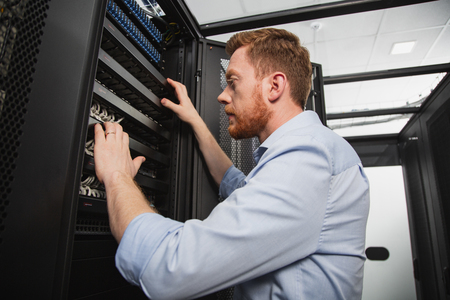 Computer equipment. Low angle of determined IT technician studying server closet while standing