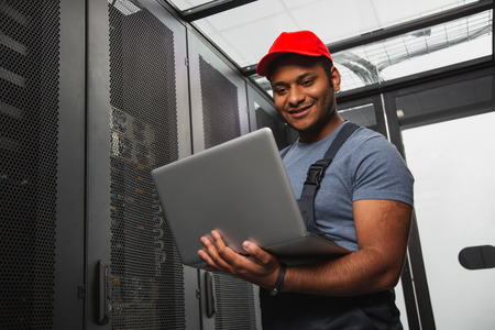 Effective IT system. Low angle of jolly IT engineer smiling and holding laptop