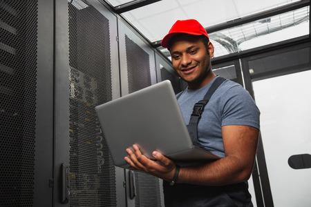 Sistema de TI eficaz. Ángulo bajo de alegre ingeniero de TI sonriendo y sosteniendo portátil