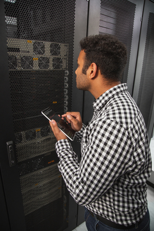 Clever IT Guy Regarding Server Closet And Using Tablet Stock Photo    102433122