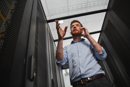 Perform troubleshooting. Low angle of successful IT guy walking in server closet and gesturing Stock Photo