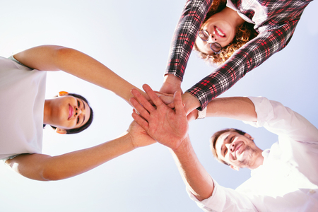 Our success. Cheerful young colleagues smiling and holding their hands Stock Photo