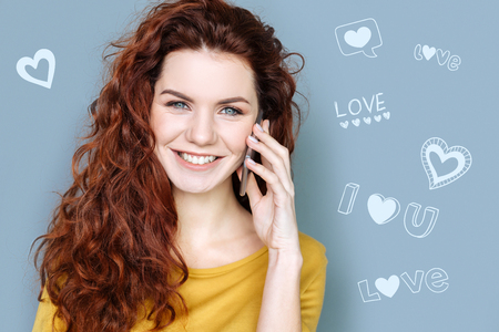 Talking with boyfriend. Emotional student looking happy and smiling while having a pleasant phone talk with her boyfriend