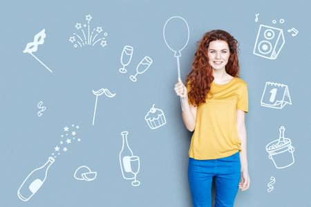 Birthday party. Cheerful friendly young woman smiling while holding a lovely balloon and enjoying her birthday party Stock Photo