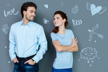 Loving couple. Beautiful young woman standing with her arms crossed and smiling to her handsome kind boyfriend