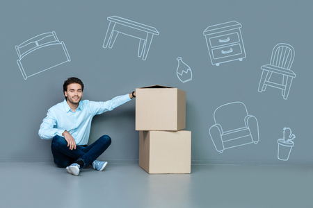 Happy to move. Positive young man sitting on the floor after moving to a new flat with carton boxes by his side
