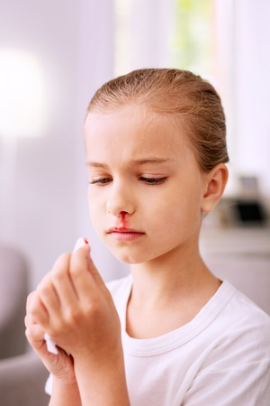 My blood. Sad cheerless girl looking at the paper tissue while having wiping blood with it
