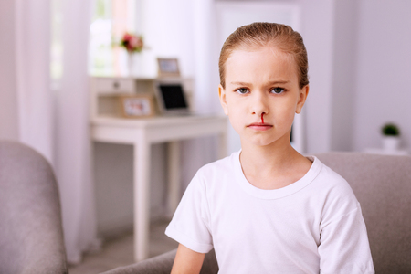 Being sick. Unhappy young girl looking at you while feeling sick