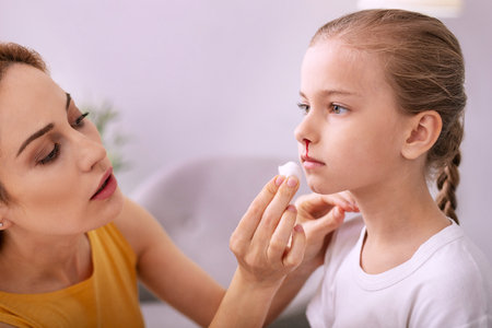 Caring mother. Nice young woman looking at her daughter face while wiping away her blood Stock Photo