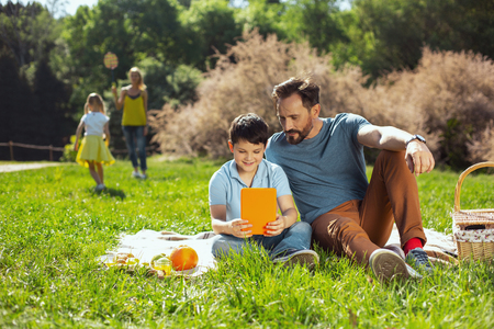 Best friends. Inspired lovely boy holding a tablet while sitting with his father in the park