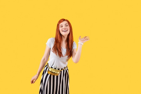 Cheerful smile. Joyful attractive woman standing against yellow background while greeting you