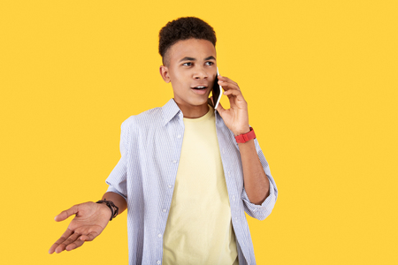 In touch. Nice handsome man having a phone conversation while standing against yellow background Banco de Imagens