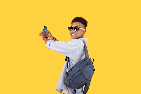Young traveler. Pleasant handsome man turning to you while holding a smartphone in his hands Stock Photo - 103508063