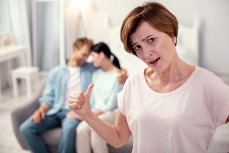 Infeliz suegra. Mujer anciana triste mirándote mientras se preocupa por su hijo Foto de archivo