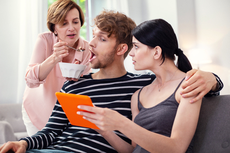 You are hungry. Pleasant caring woman feeding her song while caring about him Stock Photo