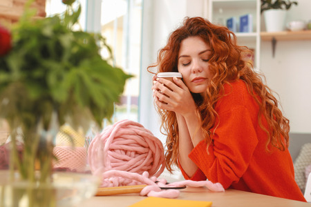Feeling relieved. Appealing woman with long red curly hair feeling extremely relieved while drinking coffee after long workday Stok Fotoğraf