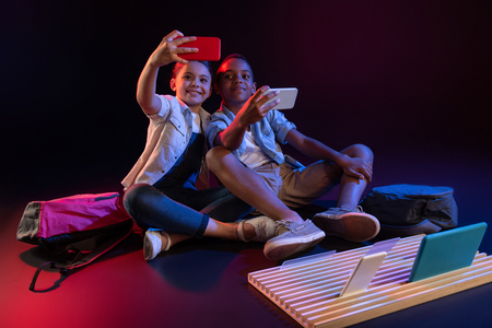 Say cheese. Alert adorable boy and a girl smiling and taking selfies while sitting on the floor