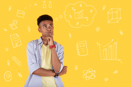 Difficult task. Clever serious teenager frowning and touching his face while trying to cope with a difficult task at the lesson Stock Photo