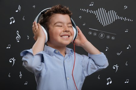 Amazing music. Happy little boy looking excited and standing with his eyes closed while listening to music in big headphones
