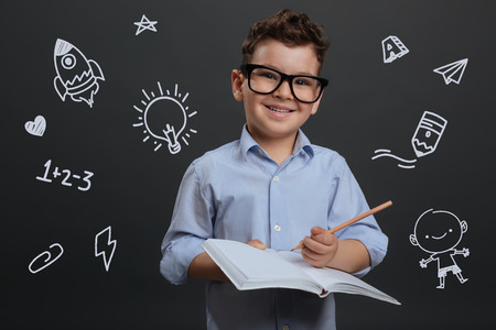 Knowledge. Cheerful smart little boy smiling and looking curious while standing with a pencil in his hand and making notes Banco de Imagens