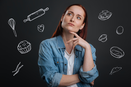 Thoughtful cook. Qualified professional cook touching her face and looking into the distance while thinking about a new unusual meal Banco de Imagens
