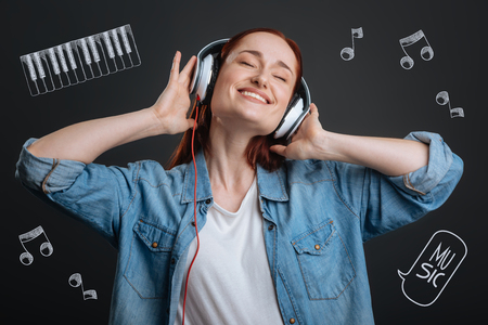 Relaxing with music. Positive happy young woman feeling good and relaxed while wearing big headphones and listening to music