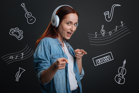 Music lover. Emotional active young person wearing casual clothes and looking positive while listening to music in big headphones