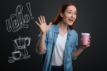 Exciting meeting. Positive emotional young woman standing with a cup of coffee and waving her hand while noticing an old friend