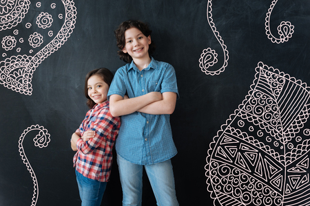 Friendly children. Little cheerful girl having her arms crossed and smiling happily while standing next to her positive elder brother Banco de Imagens