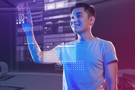 Exciting work. Cheerful emotional young programmer feeling excited and smiling while standing alone and touching the holographic image