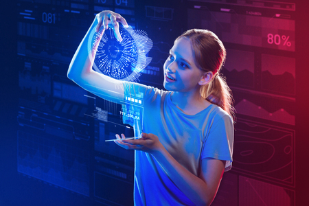 Holding a hologram. Cheerful emotional schoolgirl smiling and feeling impressed while standing with a modern smartphone and holding a wonderful bright hologram in her hand Foto de archivo