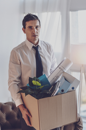 Bad mood. Cheerless young man looking at you while holding a box with his stuff