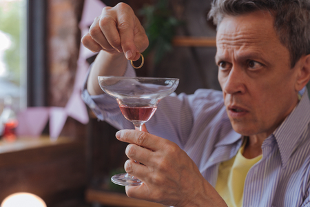 Ring in cocktail. Earnest mature man holding glass and placing ring in it Stock Photo