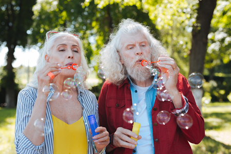 Soap bubbles. Pleasant aged people blowing soap bubbles while having fun together