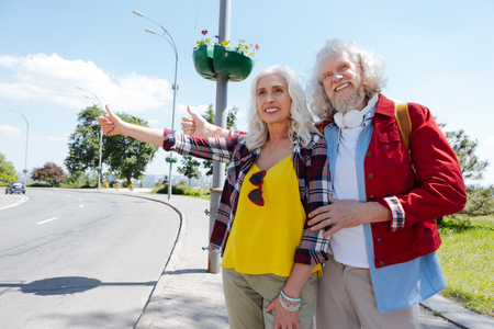 Hippy lifestyle. Aged hippy couple standing at the roadside while asking for a ride