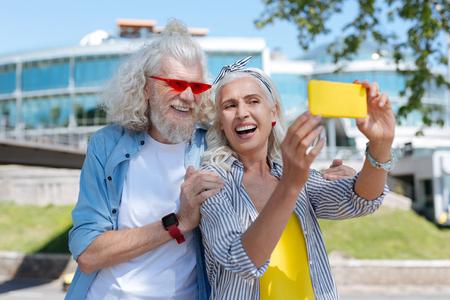 Radosny nastrój. Wesoła pozytywna kobieta robi selfie będąc razem z mężem Zdjęcie Seryjne