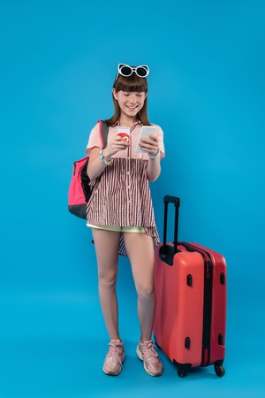In high spirits. Cheerful charming girl standing near her luggage and using her phone
