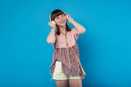 Great day off. Exuberant charming girl holding her headphones and listening to music Stock Photo