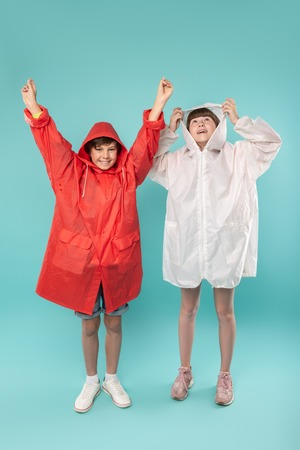 So comfy. Alert sweet kids standing next to each other and wearing raincoats