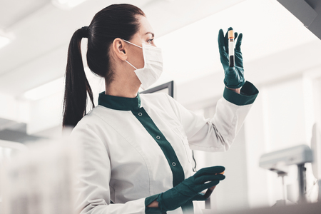 DNA. Profile of experienced concentrated doctor holding blood sample and scrutinizing it while standing in modern laboratory