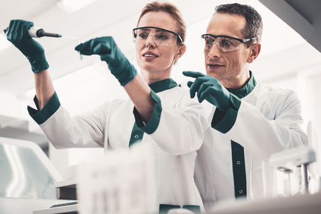 Analyzing. Portrait of hardworking doctors wearing glasses and dropping samples in a test tube while expressing interest Foto de archivo