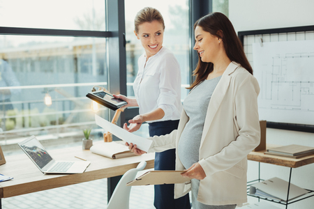 Maternity leave. Kind clever cheerful boss smiling while taking maternity leave documents from her happy pregnant employee