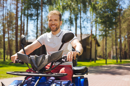 I adore driving. Cheerful young man smiling and driving an all-terrain vehicle Stock Photo