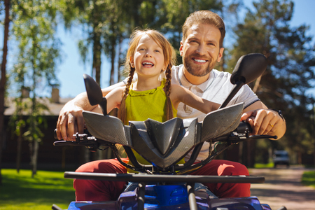 Interesting activity. Alert charming girl smiling and driving ATV with her daddy Banque d'images