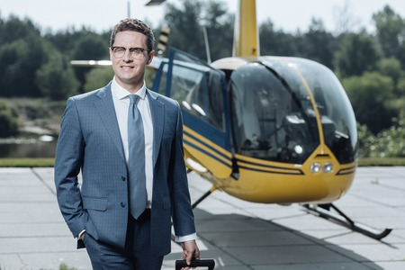 Great deal. Cheerful young CEO in a suit smiling at the camera while leaving a helipad after taking a flight and securing a deal