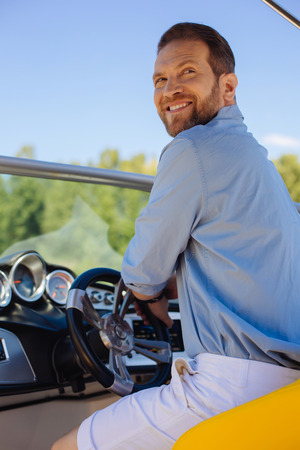 Who is here. Charming young man sitting behind the steering wheel of a yacht and turning around with a smile on his lips while being called by someone Imagens